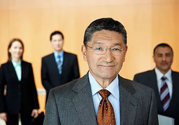 man in glasses and suit with people in background