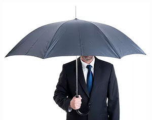man in suit under umbrella